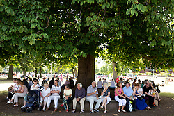 © Licensed to London News Pictures. 24/07/2013. Stratford upon Avon, Warwickshire, UK. As temperatures rise after the recent thunderstorms and rain, people flocked to Stratford upon Avon to start enjoying the sun. Pictured, finding a bit of shade to enjoy an ice cream and the summer warmth. Photo credit : Dave Warren/LNP