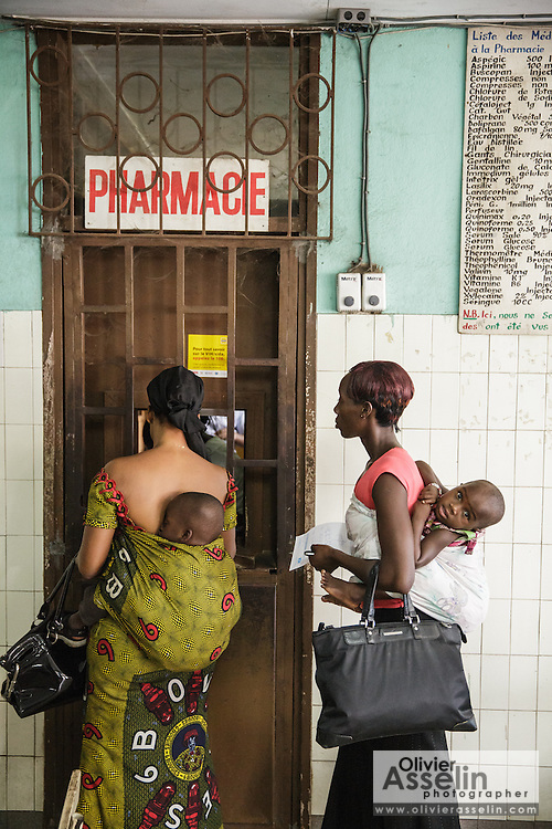 Women pick up prescriptions from the pharmacy at the Koumassi General hospital in Abidjan, Cote d'Ivoire on Friday July 19, 2013.