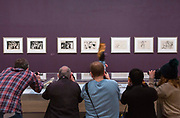 UNITED KINGDOM, London: 06 March 2018 Photographers take a picture as a visitor walks past a collection of Picasso prints at The Tate Modern's new exhibition 'Picasso 1932: Love, Fame, Tragedy'. The exhibition, which consists of a wide range of Picasso works, runs from 8th March - 9 September 2018.  Rick Findler / Story Picture Agency