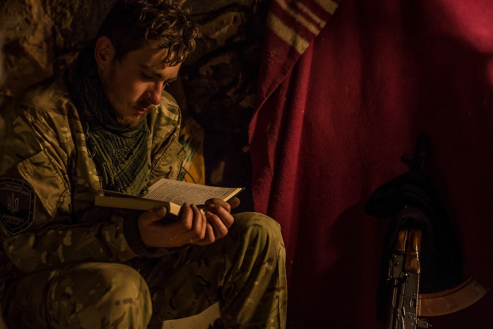 """PERVOMAISKE, UKRAINE - NOVEMBER 17, 2014: """"Patrick,"""" a member of the 5th platoon of the Dnipro-1 brigade, a pro-Ukraine militia, who chose not to give his name because he is from a nearby town and fears for the safety of his family, reads a book inside a bunker where he sleeps at their post underneath a bridge in Pervomaiske, Ukraine. CREDIT: Brendan Hoffman for The New York Times"""