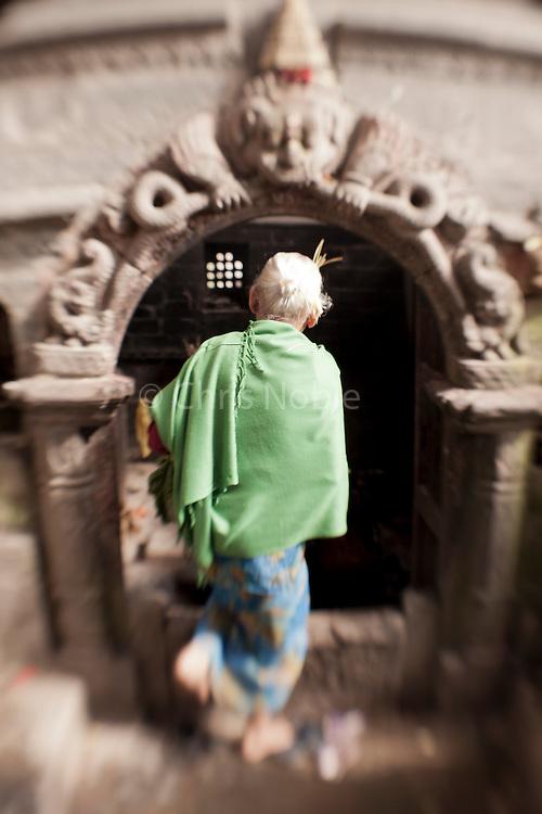 An elderly woman visits a shrine in Nepal's Bhaktapur Village.
