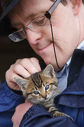 Man with learning disability on trip to farm stroking a kitten