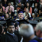 Goldey-Beacom graduate Chris Gebhart, CENTER, peeks over the crowd during Goldey-Beacom commencement exercise Friday, May 1, 2015, at Joseph West Jones College Center on the campus of Goldey-Beacom College in Wilmington Delaware.