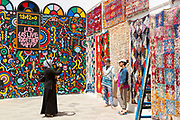 Tourists visit and take photos next to street art murals painted on the walls and architecture inside the seaside town during the International Cultural Festival, Asilah, Northern Morocco, 2015-08-11. <br />