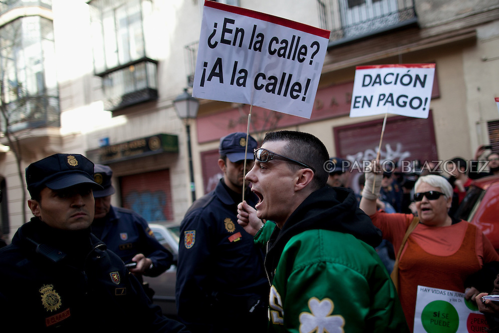 Anti eviction activists shout slogans and hold placards reading 'In the street? To the street' next to riot police during an 'escrache' near the house of Spain's President of Parliament Jesus Posadas on April12, 2013 in Madrid, Spain. The Mortgage Holders Platform (PAH) and other anti evictions organizations have been organizing 'escraches' for several weeks under the slogan 'There are lives at risk' to claim the vote for a Popular Legislative Initiative (ILP) to stop evictions and facilitate social rent, outside Popular Party deputies' houses and offices. 'Escraches' are a form of peaceful protest that were used in Argentine in 1995 to publically denounce pardoned members of the dictatorship for their crimes at their doorsteps.