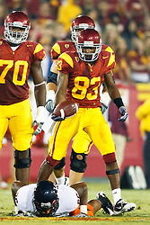 September 11, 2010; Los Angeles, CA, USA;  Southern California Trojans wide receiver Ronald Johnson (83) stands over Virginia Cavaliers linebacker Ausar Walcott (26) after a pass reception during the first quarter at the Los Angeles Memorial Coliseum.