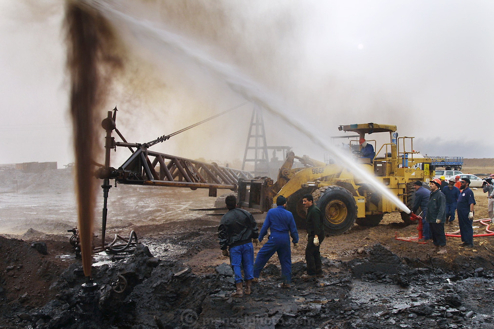 "Firefighters from the KWWK (Kuwait Wild Well Killers) attempt to kill an oil fire in the Rumaila field by guiding a ""stinger"" that will pump drilling mud into the damaged well. A ""stinger"" is a tapered pipe on the end of a long steel boom controlled by a bulldozer. Drilling mud, under high pressure, is pumped through the stinger into the well, stopping the flow of oil and gas. A sudden wind shift after a sandstorm caused the oil to blow back on the workers and equipment, causing a very dangerous situation because the oil and gas could have easily ignited. The Rumaila field is one of Iraq's biggest oil fields with five billion barrels in reserve. Many of the wells are 10,000 feet deep and produce huge volumes of oil and gas under tremendous pressure, which makes capping them very difficult and dangerous. This well is of relatively low volume. Rumaila is also spelled Rumeilah.     ."
