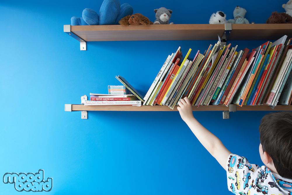 Boy (5-6) choosing book from shelf back view