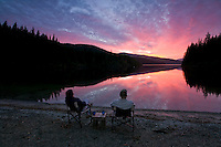 A spectacular sunset over Stella Lake, north of Campbell River, highlights campers, relaxing and catching the last rays of the day.  Stella Lake, Vancouver Island, British Columbia, Canada.
