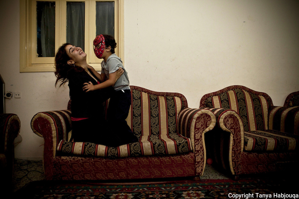 Journalist and outspoken Hamas critic, Asmaa Al Ghoul, plays with her son [Tanya Habjouqa]