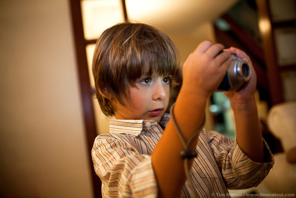 A six year-old boy uses a point and shoot camera to take pictures inside.