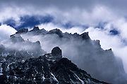 Relentless Patagonian winds pull low clouds across a barren ridgeline in Torres del Paine National Park, Chile.