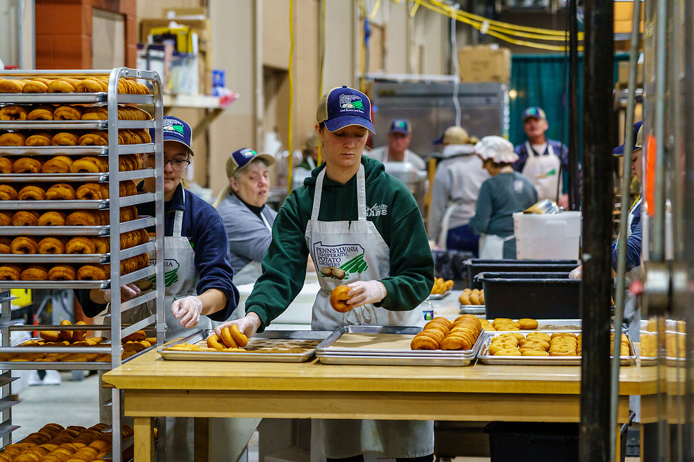 Harrisburg, PA / USA - January 9, 2020: Workers prepare potato doughnuts, which is one of the many items for sale at the PA Farm Show in the food court.