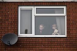 © Licensed to London News Pictures . 20/01/2018. Doncaster, UK. Children look out of a first floor window as far-right street protest movement , the English Defence League ( EDL ) , hold a demonstration , opposed by anti-fascists , including Unite Against Fascism ( UAF ) in a park in Hexthorpe in Doncaster . EDL supporters chanted anti-Roma slogans as they marched through the town . Photo credit: Joel Goodman/LNP