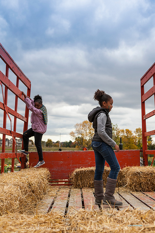 Children having fun on a hay ride in autumn.