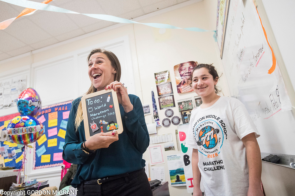 Cara Nelson, left, a seventh grade social studies teacher at East Hampton Middle School, is presented with a present from seventh grader Olivia Masone, 12, upon returning from her recent trip that involved running seven marathons in seven days on seven continents, in East Hampton, Feb. 7, 2018. This was Nelson's first day back to school after finishing her last marathon on Monday in Miami.