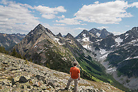 Adult male hiker with red jacket on Ragged Ridge taking in the view of Upper Fisher Creek Basin. Mount Logan is in the distance. North Cascades National Park Washington