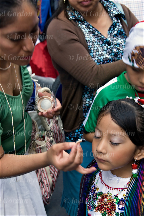 Mother applies makeup to young daughter as Mexican Americans show ethnic pride during the Mexican Day Parade (or Mexican Independence Parade) celebrates Mexico's independence from Spain. It is a celebration that brings together many colorful floats, musical and artistic groups, dancers representing different regions of Mexico.Their music, costumes and celebration showcase the diversity that makes New York unique.