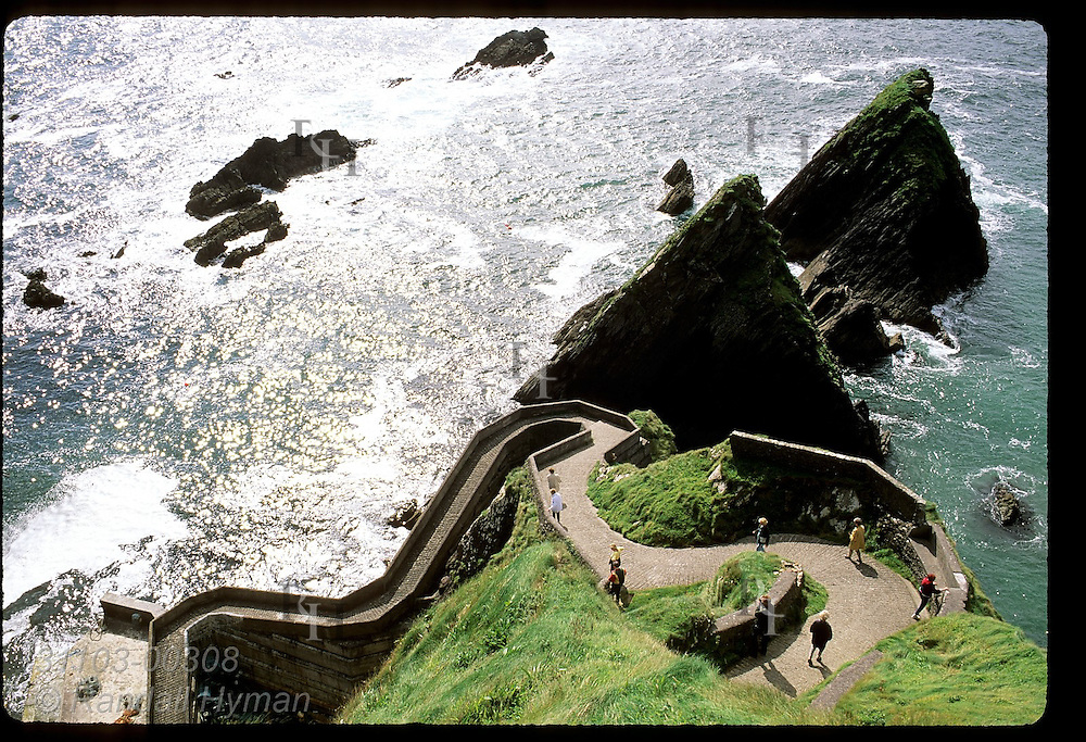 Tourists walk down Dunquin Pier, traditional departure point for Great Blasket Island; Dingle Peninsula, Ireland.