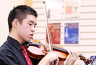 Centerville High School Orchestra member Justin Lun performs holiday music at the WashingtonCenterville Public Library in Centerville, Monday, December 5, 2011.