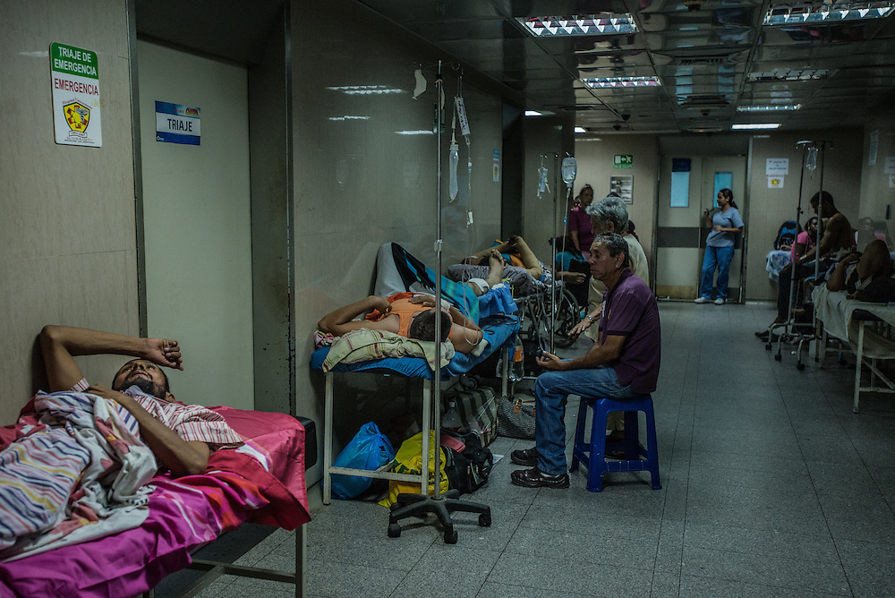 PUERTO LA CRUZ, VENEZUELA - APRIL 16, 2016: The emergency room is so overcrowded with patients waiting for treatments, that they spill out into the hallway.  Hospital Universitario Dr. Luís Razetti is one of the worst state-run, public hospitals in Venezuela.  Doctors compare it to working in a war zone - they regularly have to turn patients away, because they don't have the majority of medicines  or medical equipment and supplies needed to give them medical attention.  When they do accept patients, they have to work with extremely limited resources, because they don't have the supplies they need for things like X-Rays,  and many exams nd operations.  The hospital's infrastructure is crumbling, and staff don't have all the cleaning supplies required to keep the hospital sanitary. The hospital also suffers from weekly shortages of running water and electricity.  In April, several babies died when a power outage turned off the incubators, and the hospital's generator failed to work because of lack of maintenance.  The same month, authorities found over 100 pieces of medical equipment, stolen from the hospital in the home of the assistant to the hospital's director.  Despite having the largest oil reserves in the world, falling oil prices and wide-spread government corruption have pushed Venezuela into an economic crisis, with the highest inflation in the world and chronic shortages of food and medical supplies.  PHOTO: Meridith Kohut