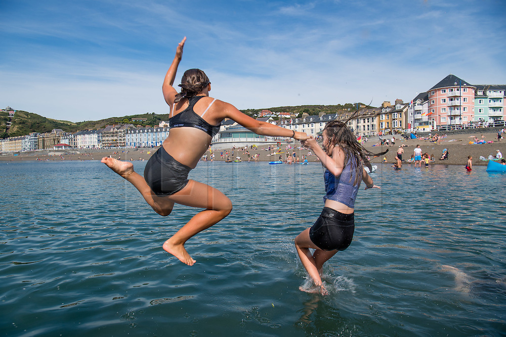 © London News Pictures. 16/08/0216. Aberystwyth, UK. Teenagers on their long summer holidays cool off on a hot summer afternoon by jumping into the clear sea off the wooden jetty dock pier at Aberystwyth on the west wales coast . The weather is set to improve even more tomorrow, culminating in a mini-heatwave, with temperatures forecast to reach the high 20s or low 30s centigrade in parts of the UK. Photo credit: Keith Morris/LNP