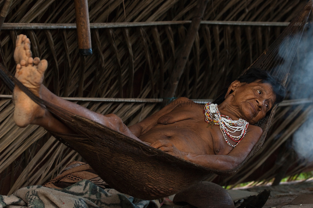 Huaorani woman, Mima sitting in a hammock which is usually the only furniture in the home.<br /> Bameno Community. Yasuni National Park.<br /> Amazon rainforest, ECUADOR.  South America<br /> This Indian tribe were basically uncontacted until 1956 when missionaries from the Summer Institute of Linguistics made contact with them. However there are still some groups from the tribe that remain uncontacted.  They are known as the Tagaeri &amp; Taromenane. Traditionally these Indians were very hostile and killed many people who tried to enter into their territory. Their territory is in the Yasuni National Park which is now also being exploited for oil.