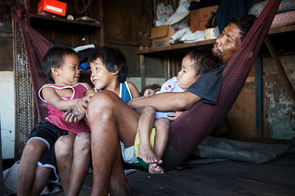 Arnulfo Aragon, 42 with children (L to R)  Gian Aragon, 5, Glen-Rose Aragon, 7 and Rose-Ann Aragon, 2. Arnulfo lost his wife due to kidney complications after the delivery of 2 year old Rose-Ann. His wife was an alcoholic. Arnulfo himself suffers from severe pains in his joints and his arms and legs. At times he can't use his hands. He has never gone to the doctor to be diagnosed. He can't work or look after his three small children. His mother has breast cancer and his father, 70 year old Renerio, is the children's main caretaker. They make a living from a games table and Renerio carries water for people. They live in a slum area. Tondo, Manila, Philippines.