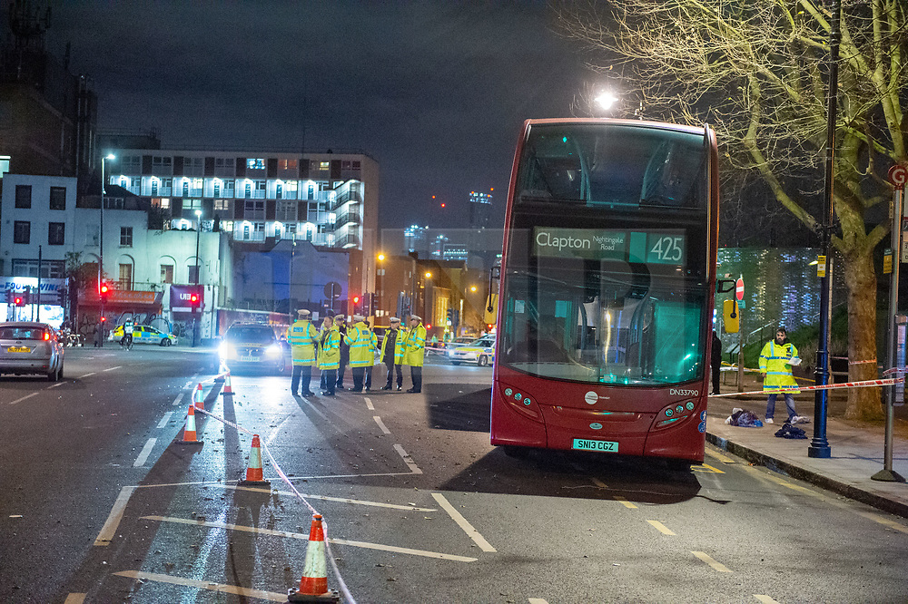 © Licensed to London News Pictures. 05/12/2019. London, UK. A Route 425 London bus sits inside a police cordon as an investigation is carried out after a pedestrian - a woman in her 50's - was involved in a collision near the junction of Mile End Road. The woman was taken to an East London hospital in a serious condition. Photo credit: Peter Manning/LNP