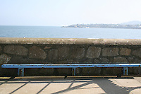 View from Dun Laoghaire Pier towards Sandycove, blue bench in foreground. County Dublin, Ireland