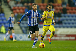 Chris McCann of Wigan is challenged by Lewis McGugan of Sheffield Wednesday - Photo mandatory by-line: Rogan Thomson/JMP - 07966 386802 - 30/12/2014 - SPORT - FOOTBALL - Wigan, England - DW Stadium - Wigan Athletic v Sheffield Wednesday - Sky Bet Championship.