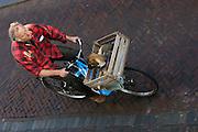 Een man fietst met zijn hond in een krat voorop de fiets over de Oudegracht in Utrecht