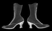 An x-ray image of a pair of Victorian ladies dress shoes or boots.  These high heel boots made in the 1880's are almost identical to modern design.  Of particular importance is the boots have nails in the heels holding together multiple layers of leather.  The shoes also have metal shavings placed between the sheets of leather to keep the different layers from sliding.  The shoe is fully laced up, but the cotton laces are all but invisible to these low level x-rays.