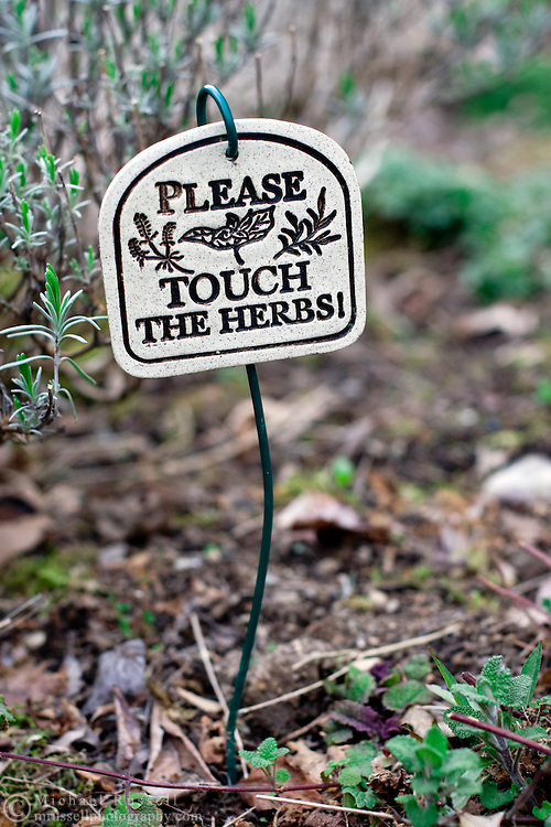 A ceramic sign in a Herb Garden - Please Touch the Herbs.