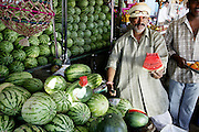 A market vendor in Ujjain offers a taste of his produce in hopes that the taster will buy an entire watermelon. (Supporting image from the project Hungry Planet: What the World Eats.) Grocery stores, supermarkets, and hyper and megamarkets all have their roots in village market areas where farmers and vendors would converge once or twice a week to sell their produce and goods. In farming communities, just about everyone had something to trade or sell. Small markets are still the lifeblood of communities in the developing world.