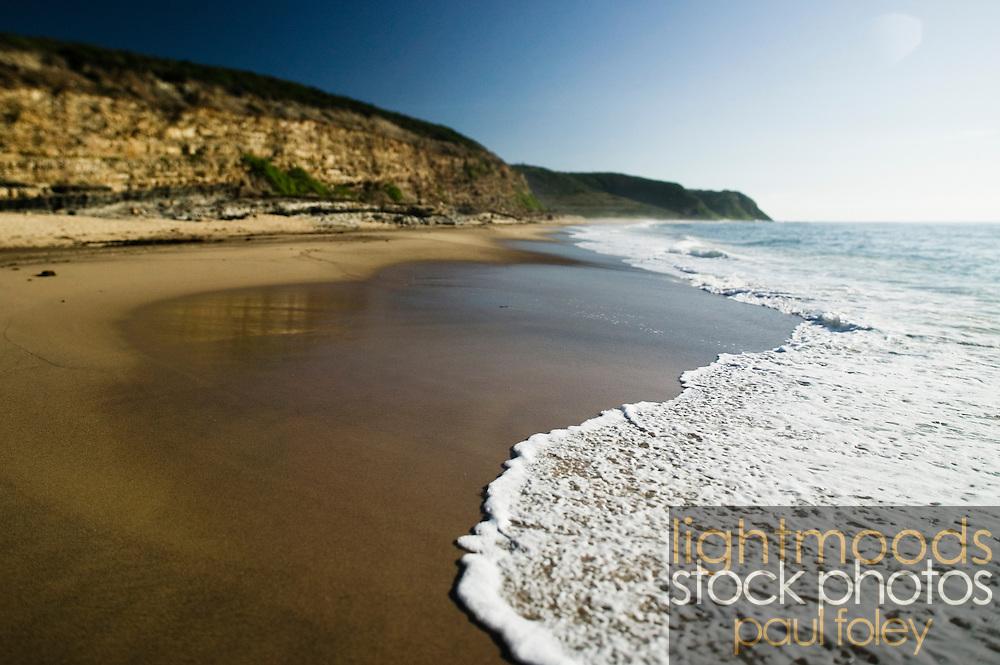 Selective focus close up views of foam and sand. East Coast Australia.