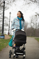 Mother walking with baby carriage in park