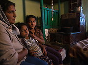 A Roma woman and two of her daughters sit on a bed in their home in the farming village of  Dimacheni in Botosani County, Romania. She lives with her husband and their children in a two-room house. The stove in the picture is used both for cooking and for heating up the room.
