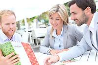 Businesspeople deciding menu at sidewalk cafe