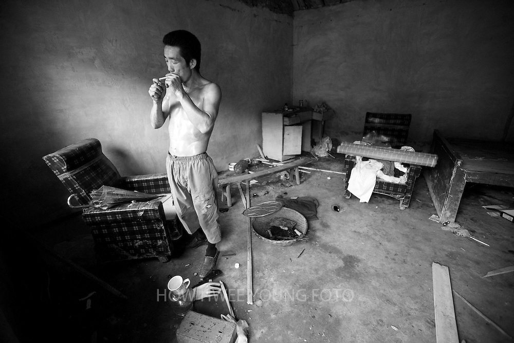 A villager of lights his cigarette in his relative's demolished home before relocation to neighbouring Hui county to make way for the colossal South-to-North Water Transfer project in Xichuan county of Henan Province in China on 28 June 2010.  The South-to-North Water Transfer project, the largest known water diversion project, was conceived in 1952 to solve the country's chronic water shortages and involves creating three routes to channel 44.8 billion cu m of water from southern China to the northern areas. As part of the project's central route, affecting Henan and Hubei provinces, water from the Danjiangkou reservoir will be diverted to Beijing. The central route, which will raise the height of the Danjiangkou reservoir dam from 162 meters to 176.6 meters, requires the relocation of 330,000 people in Henan and Hubei provinces. Parts of Xichuan county, a remote, mountainous region inaccessible by railway and home to 162,000 migrants, the most anywhere, will be completely submerged by water from the Danjiangkou reservoir by 2014. The vast resettlement of affected residents in Xichuan county began in August 2009 and lasted till 2011.