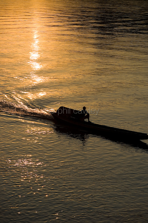 Laos - mekong river, silhouette of a small boat traveling downstream