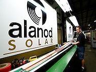 Laser technician Roy Owens works with solar fins for solar heating units at Alanod Westlake Metals in North Ridgeville, OH.