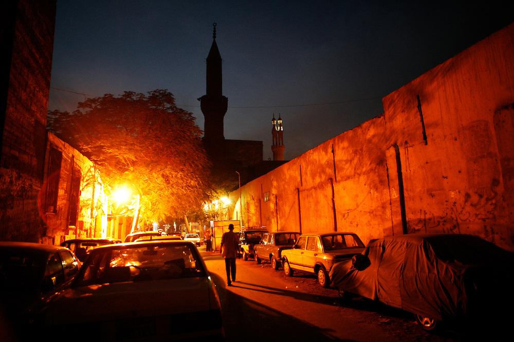 A man walks down a Cairo street at night.
