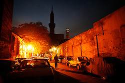A man walks down a Cairo street at night.