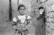 Two young girls, one hiding in alley