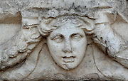 Mask and garland frieze from the Portico of Tiberius on the Southern portico of the Agora, 1st century AD, Aphrodisias, Aydin, Turkey. The Sculpture School at Aphrodisias was an important producer of carved marble sarcophagi and friezes from the 1st century BC until the 6th century AD. The Portico of Tiberius was built under the reign of Tiberius and has many examples of mask and garland friezes, consisting of the heads of gods, goddesses, theatrical characters, mythological figures or masks, each with a distinct facial expression, between hanging garlands of leaves, fruit and flowers. This example shows a sorrowful female face. Aphrodisias was a small ancient Greek city in Caria near the modern-day town of Geyre. It was named after Aphrodite, the Greek goddess of love, who had here her unique cult image, the Aphrodite of Aphrodisias. The city suffered major earthquakes in the 4th and 7th centuries which destroyed most of the ancient structures. Picture by Manuel Cohen