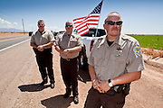 04 AUGUST 2010 -- GILBERT, AZ: Mariciopa County Deputy Hanse (CQ HANSE), Detention Officer Horton (CQ) and Detention Officer London (CQ) LEFT TO RIGHT, BACKGROUND TO FOREGROUND, wait for Det. Carlos Ledesma's cortege to pass at the funeral for Chandler police detective Carlos Ledesma Wednesday. They are members of the azhighwayofheroes.com organization, which honors fallen first responders. Ledesma was killed during a shoot out with suspected drug dealers during an undercover operation in south Phoenix Wednesday July 28.  PHOTO BY JACK KURTZ   THEY SAID LAST NAMES ONLY