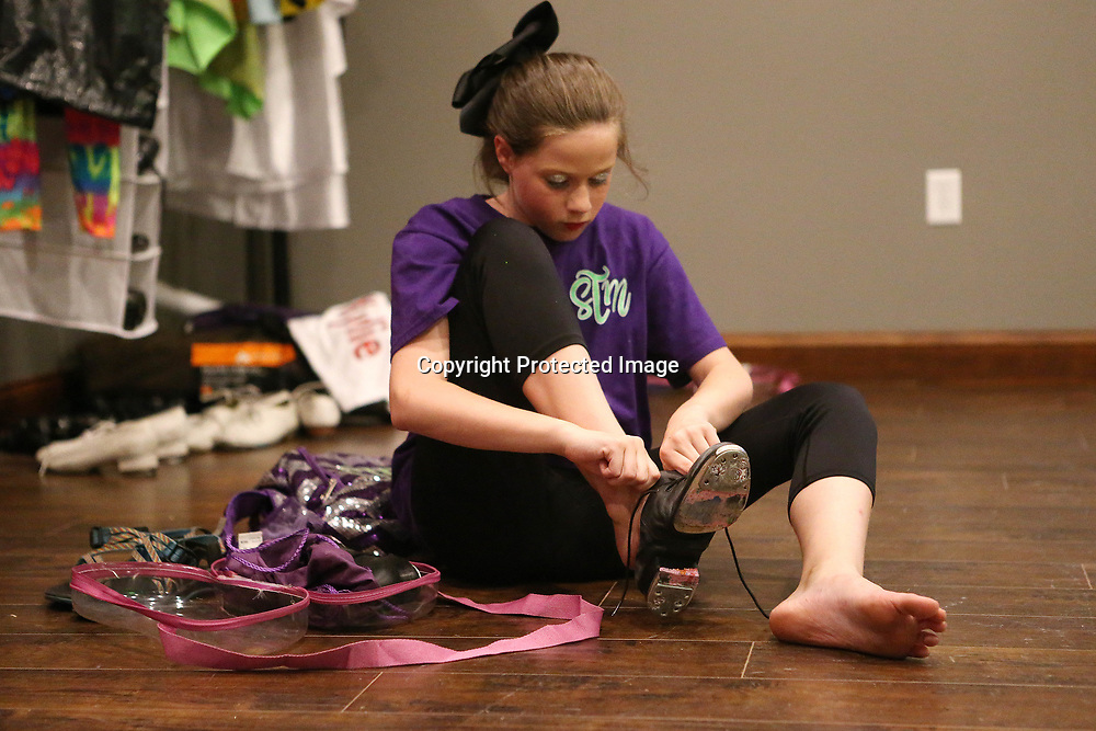 Clogger Kylie Vail, 11, puts on her clogging shoes before the start of practice at the Steel Toe Magnolias studio in Amory.
