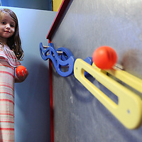 Adam Robison | BUY AT PHOTOS.DJOURNAL.COM<br /> Audrey Beal, a pre-k student at ECEC, plays the rool game in the interactive art sculpture/exhibit during class Thursday morning. The game allows children to use adjustible tracks and floor hockey balls and they can rearrange the magnetic tracks to see how fast the balls roll.