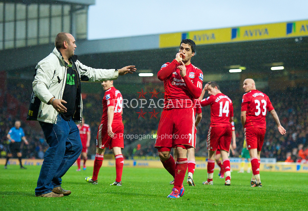 NORWICH, ENGLAND - Saturday, April 28, 2012: A Liverpool 'supporter' runs onto the pitch to congratulate Luis Alberto Suarez Diaz after his hat-trick goal sealed a 3-0 victory over Norwich City during the Premiership match at Carrow Road. (Pic by David Rawcliffe/Propaganda)